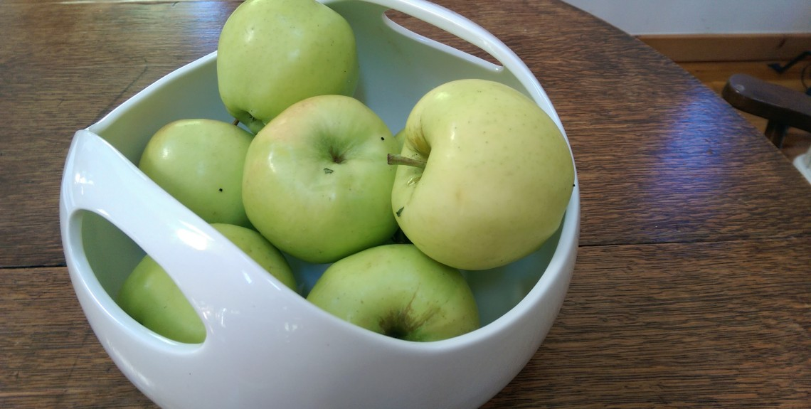 white bowl filled with green apples