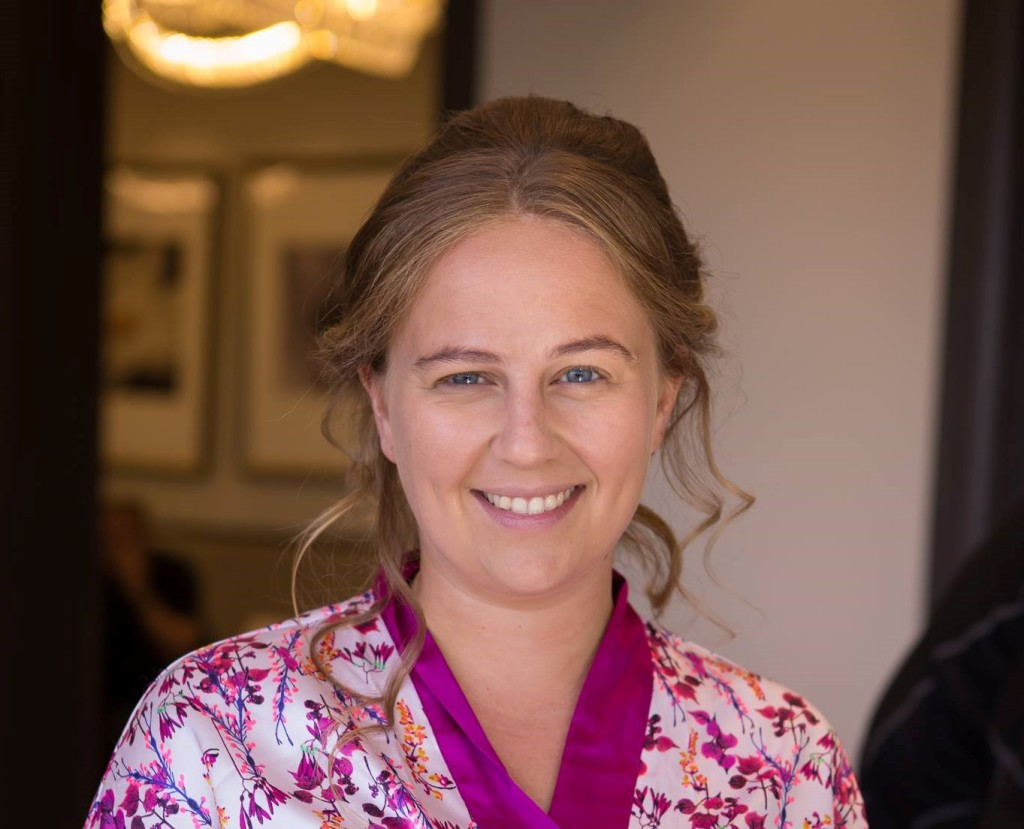 shely esses head shot. smiling female with medium length blonde hair, wearing a flowery white and purple shirt.