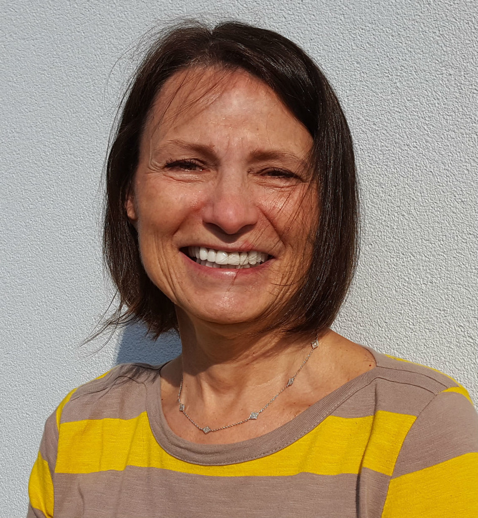 smiling female Maggie McConnell with short brown hair, wearing a yellow and brown striped shirt