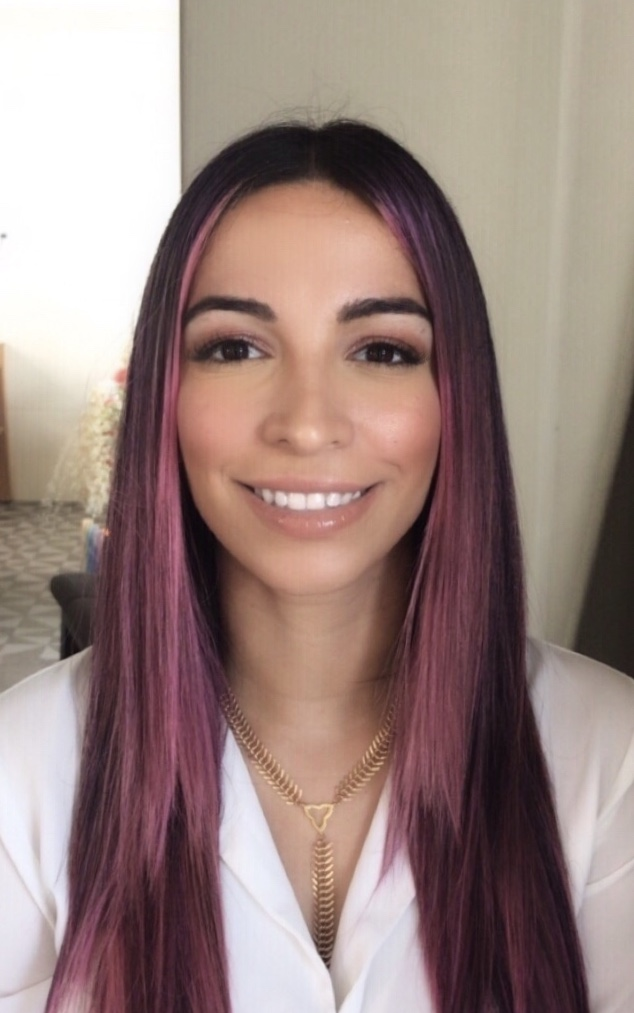 Wildilisa Silverman headshot. smiling female with long brown and purple hair, wearing a flowery white blouse and a gold necklace.
